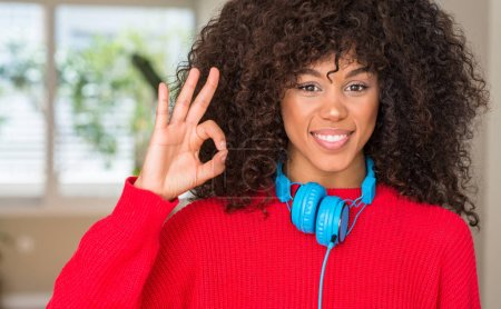 Photo for African american woman wearing headphones smiling positive doing ok sign with hand and fingers. Successful expression. - Royalty Free Image