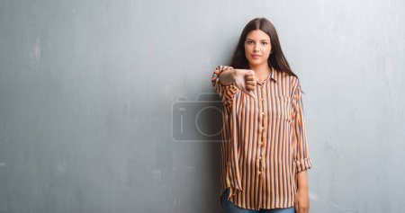 Young brunette woman over grunge grey wall looking unhappy and angry showing rejection and negative with thumbs down gesture. Bad expression.