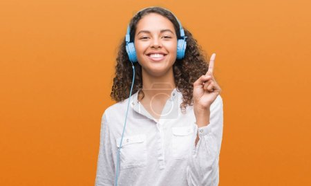 Young hispanic woman wearing headphones surprised with an idea or question pointing finger with happy face, number one