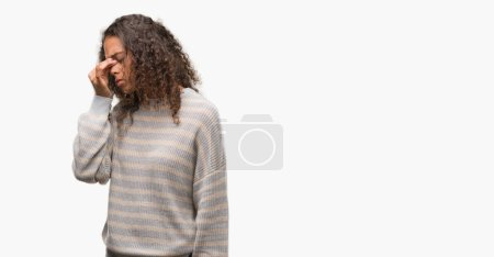 Beautiful young hispanic woman wearing stripes sweater tired rubbing nose and eyes feeling fatigue and headache. Stress and frustration concept.