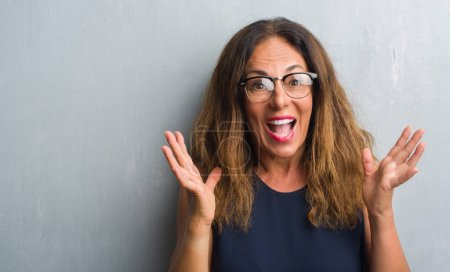 Middle age hispanic woman over grey wall wearing glasses very happy and excited, winner expression celebrating victory screaming with big smile and raised hands