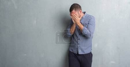 Young caucasian man over grey grunge wall with sad expression covering face with hands while crying. Depression concept.