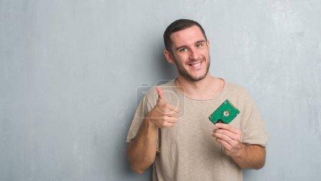 Photo pour Jeune homme caucasien sur un mur gris grunge tenant le disque dur heureux avec un grand sourire faisant signe ok, pouce levé avec les doigts, excellent signe - image libre de droit