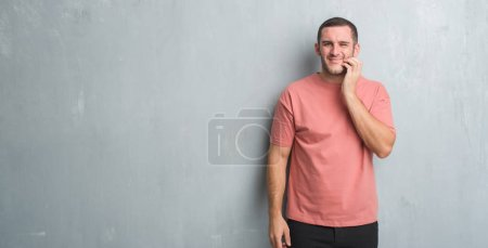 Young caucasian man over grey grunge wall touching mouth with hand with painful expression because of toothache or dental illness on teeth. Dentist concept.