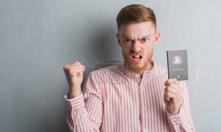 Photo for Young redhead man over grey grunge wall holding passport of Australia annoyed and frustrated shouting with anger, crazy and yelling with raised hand, anger concept - Royalty Free Image