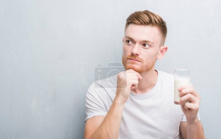 Young redhead man over grey grunge wall drinking a glass of milk serious face thinking about question, very confused idea