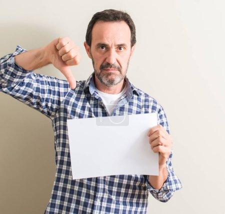 Senior homme contenant la feuille de papier vierge avec visage en colère, signe négatif montrant n'aime pas avec les pouces vers le bas, notion de rejet