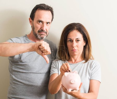 Photo for Middle age couple, woman and man, holding piggy bank with angry face, negative sign showing dislike with thumbs down, rejection concept - Royalty Free Image