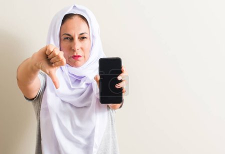 Arabian woman using smartphone with angry face, ne...