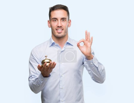 Handsome young man holding hotel ring bell doing ok sign with fingers, excellent symbol