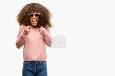 African american woman wearing pink sunglasses excited for success with arms raised celebrating victory smiling. Winner concept.