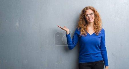Femme jeune rousse sur mur gris grunge sourire joyeux présentant et en pointant avec la paume de la main en regardant la caméra