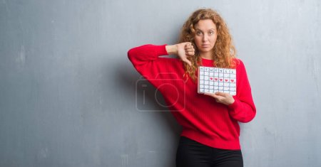 Young redhead woman over grey grunge wall holding period calendar with angry face, negative sign showing dislike with thumbs down, rejection concept