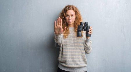 Photo pour Femme jeune rousse sur mur gris grunge, regardant à travers les jumelles avec la main ouverte, faisant signe d'arrêt avec l'expression grave et confiante, geste de défense - image libre de droit