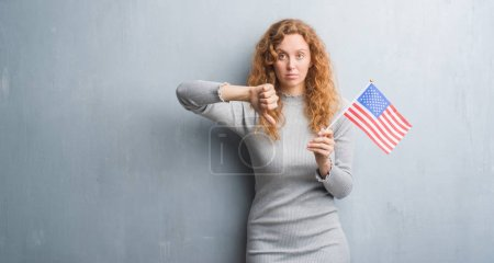 Young redhead woman over grey grunge wall holding flag of United States of America with angry face, negative sign showing dislike with thumbs down, rejection concept