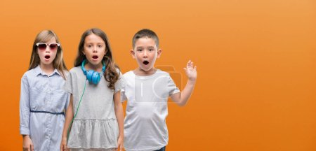 Group of boy and girls kids over orange background scared in shock with a surprise face, afraid and excited with fear expression