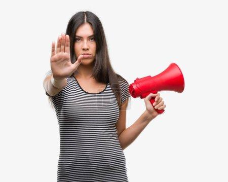 Photo pour Jeune femme hispanique mégaphone en tenant avec une main ouverte faisant signe d'arrêt avec l'expression grave et confiante, geste de défense - image libre de droit