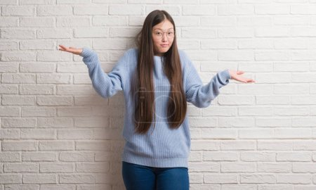 Young Chinise woman over white brick wall clueless and confused expression with arms and hands raised. Doubt concept.