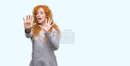 Young redhead woman afraid and terrified with fear expression stop gesture with hands, shouting in shock. Panic concept.