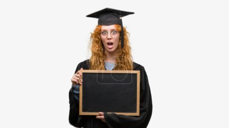 Young redhead student woman wearing graduated uniform holding blackboard scared in shock with a surprise face, afraid and excited with fear expression