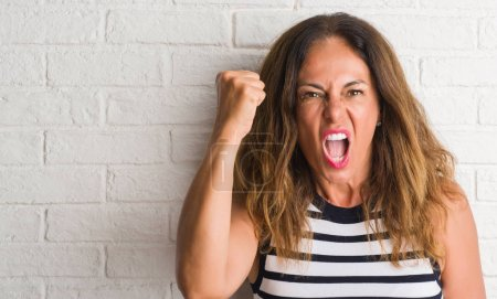 Middle age hispanic woman over white brick wall annoyed and frustrated shouting with anger, crazy and yelling with raised hand, anger concept