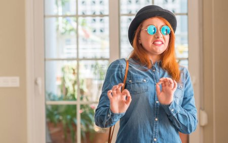 Stylish redhead woman wearing bowler hat and sunglasses disgusted expression, displeased and fearful doing disgust face because aversion reaction. With hands raised. Annoying concept.