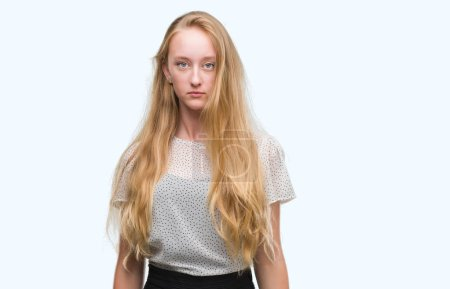 Blonde teenager woman wearing moles shirt with serious expression on face. Simple and natural looking at the camera.