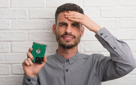 Young adult man over brick wall holding hard drive stressed with hand on head, shocked with shame and surprise face, angry and frustrated. Fear and upset for mistake.