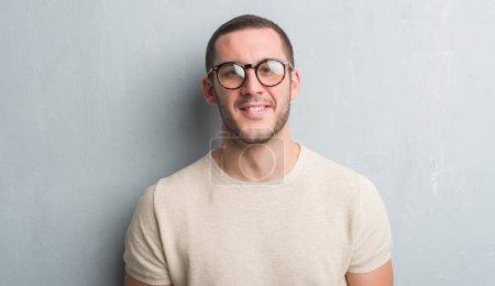 Foto de Hombre joven caucásico sobre pared gris grunge con una cara feliz de pie y sonriendo con una sonrisa de confianza mostrando los dientes - Imagen libre de derechos