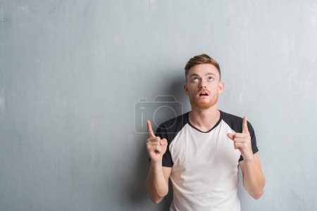 Young redhead man over grey grunge wall amazed and surprised looking up and pointing with fingers and raised arms.
