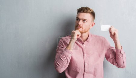 Young redhead man over grey grunge wall holding blank visit card serious face thinking about question, very confused idea