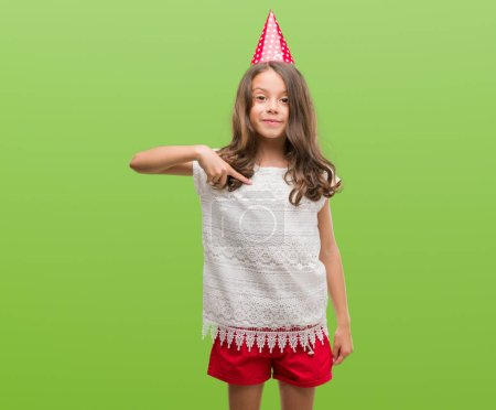 Photo pour Brunette hispanique fille portant chapeau d'anniversaire avec visage surprise pointant du doigt vers lui-même - image libre de droit