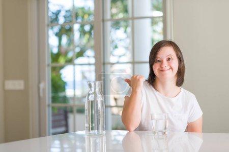 Photo pour Femme trisomique à la maison eau potable pointant et montrant avec le pouce sur le côté avec sourire heureux visage - image libre de droit