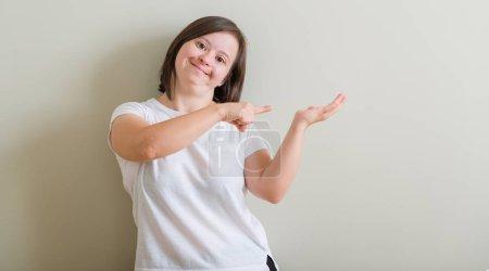 Photo pour Le syndrome de Down femme debout dessus mur étonné et souriant à la caméra tout en présentant la main et en pointant avec le doigt. - image libre de droit