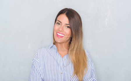 Young adult woman over grunge grey wall wearing business shirt happy face smiling with crossed arms looking at the camera. Positive person.
