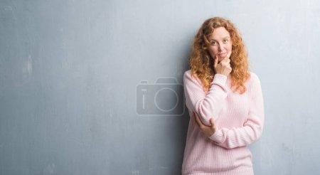 Photo pour Jeune femme rousse sur le mur gris grunge portant un pull rose regardant avec confiance la caméra avec le sourire avec les bras croisés et la main levée sur le menton. Penser positif . - image libre de droit