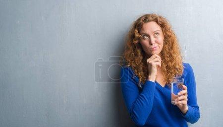 Photo pour Femme de jeune rousse plus gris grunge mur eau potable visage grave penser question, idée très confuse - image libre de droit