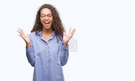 Photo pour Belle jeune femme hispanique portant lunettes expression gagnant très heureux et excité, célébrant la victoire criant avec grand sourire et a grandi à mains - image libre de droit