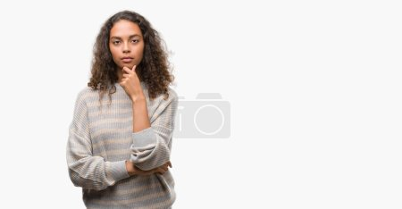 Photo for Beautiful young hispanic woman wearing stripes sweater looking confident at the camera with smile with crossed arms and hand raised on chin. Thinking positive. - Royalty Free Image