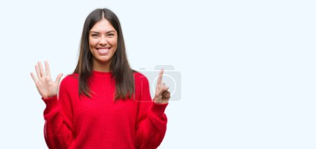 Young beautiful hispanic wearing red sweater showing and pointing up with fingers number six while smiling confident and happy.
