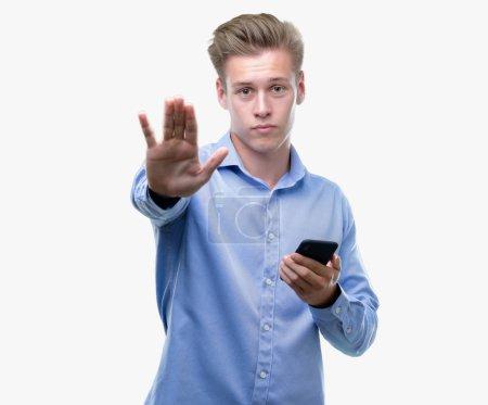 Photo pour Jeune bel homme blond, à l'aide de smartphone avec la main ouverte, faisant signe d'arrêt avec l'expression grave et confiante, geste de défense - image libre de droit