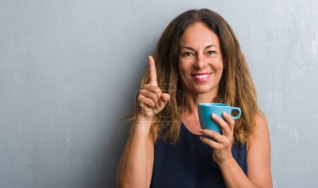 Middle age hispanic woman standing over grey grunge wall drinking cup of coffee surprised with an idea or question pointing finger with happy face, number one