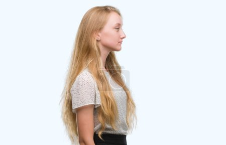 Blonde teenager woman wearing moles shirt looking to side, relax profile pose with natural face with confident smile.