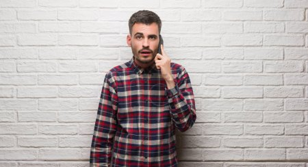 Young adult man talking on the phone standing over white brick wall scared in shock with a surprise face, afraid and excited with fear expression