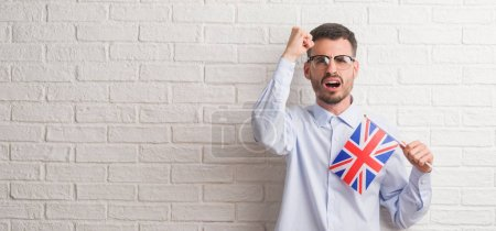 Young adult man over brick wall holding flag of United Kingdom annoyed and frustrated shouting with anger, crazy and yelling with raised hand, anger concept