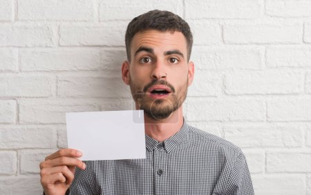 Young adult man over brick wall holding blank paper scared in shock with a surprise face, afraid and excited with fear expression