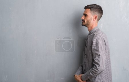 Young adult man standing over grey grunge wall looking to side, relax profile pose with natural face with confident smile.