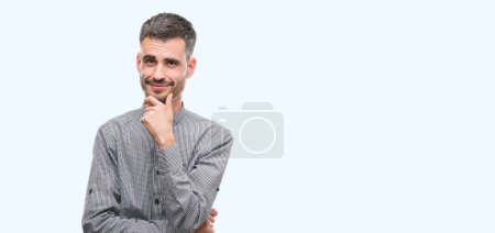 Young hipster man looking confident at the camera with smile with crossed arms and hand raised on chin. Thinking positive.