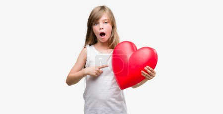 Photo for Young blonde toddler holding a red heart very happy pointing with hand and finger - Royalty Free Image