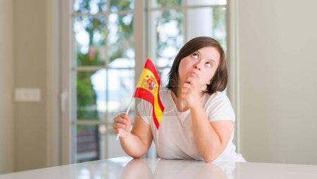 Photo pour Femme trisomique à la maison tenant drapeau de l'Espagne visage sérieux penser à la question, idée très confuse - image libre de droit